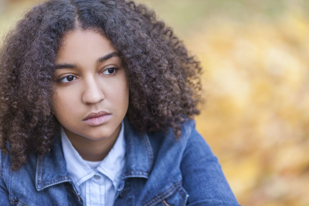 Beautiful mixed race African American girl teenager female young woman outside in autumn or fall looking sad depressed or thoughtful