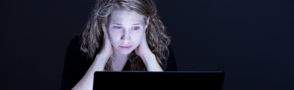 Despair sad girl looking at computer's screen