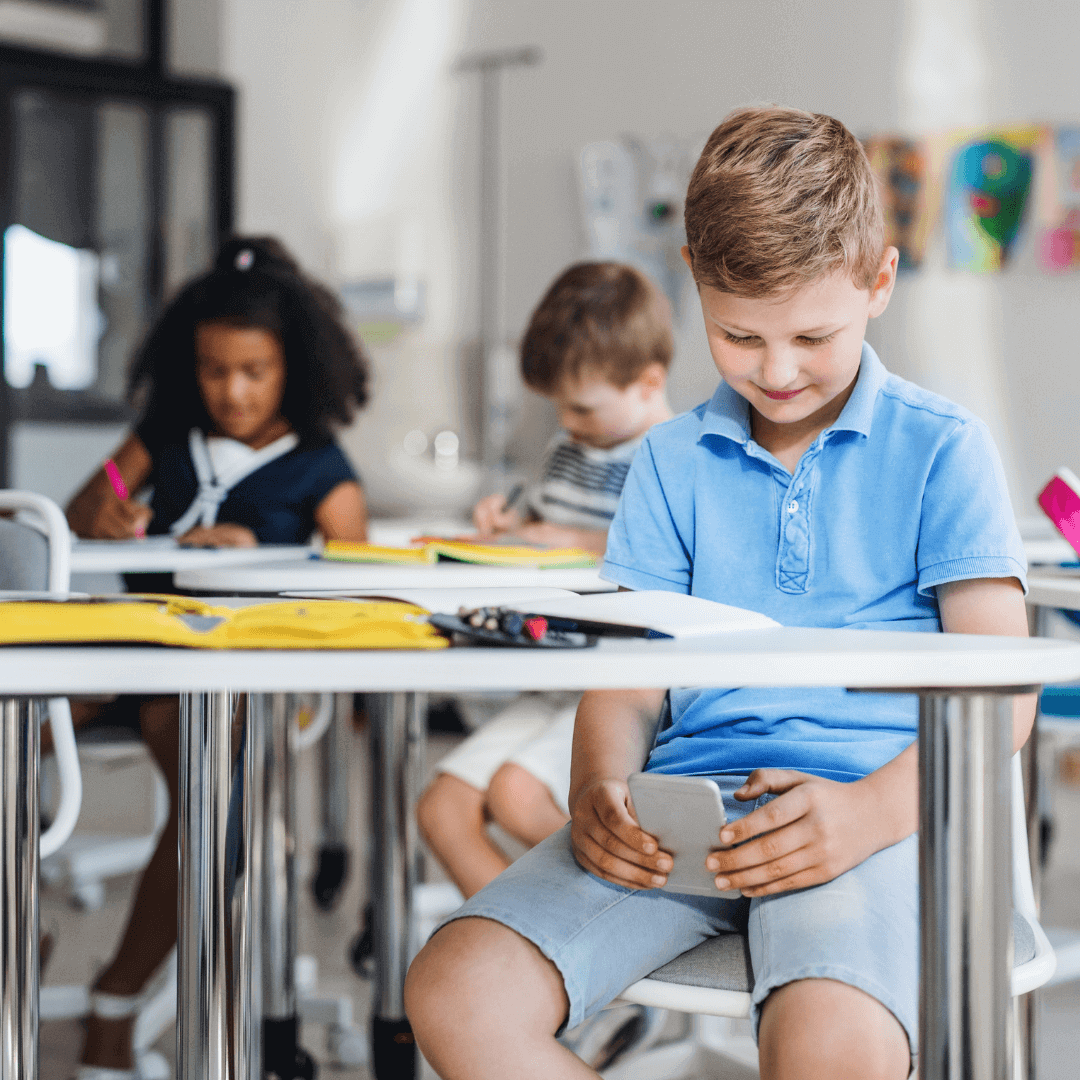 Kid using phone at school - Default2Safety Apple Campaign